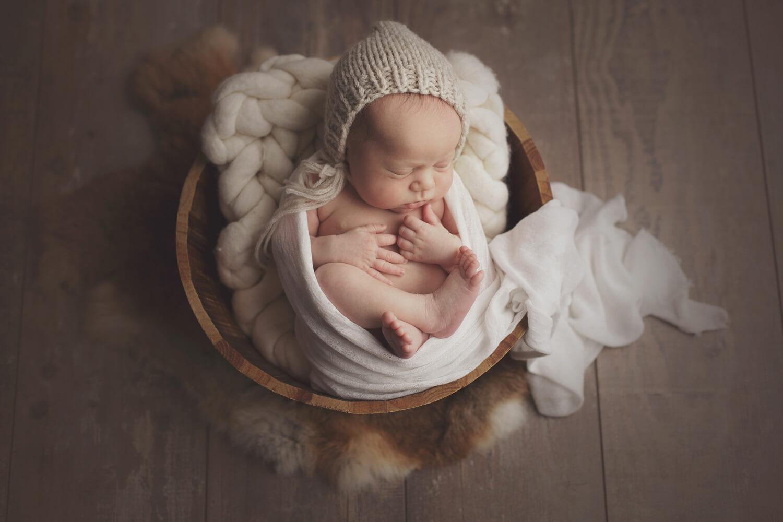 Photo d'un bébé garçon portant un bonnet dans un panier pendant la séance