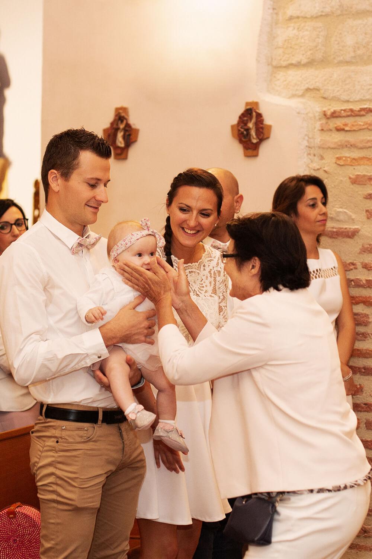 Photo d'un câlin entre mamie et petite fille pendant la cérémonie de baptême