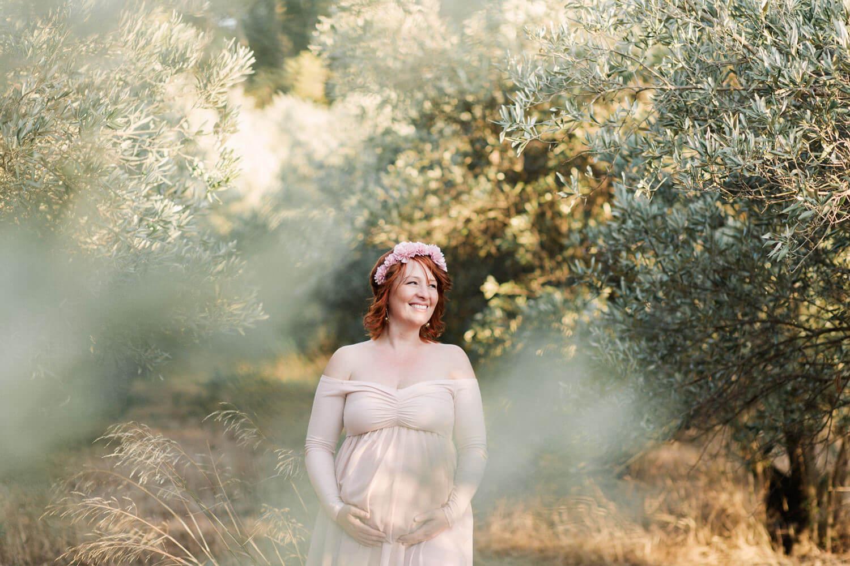 Photo d'une femme enceinte qui tient son ventre au milieu d'un champ d'oliviers près de Perpignan