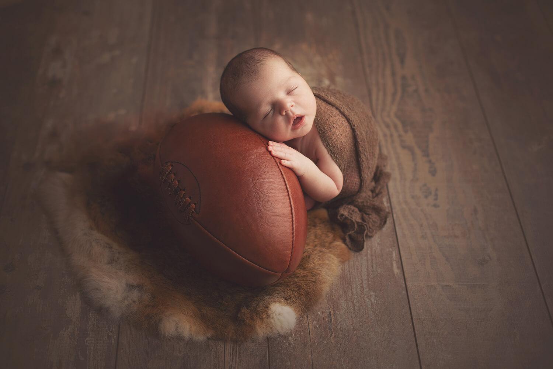 Photo d'un bebe garçon qui dort sur ballon de rugby pendant séance nouveau-né