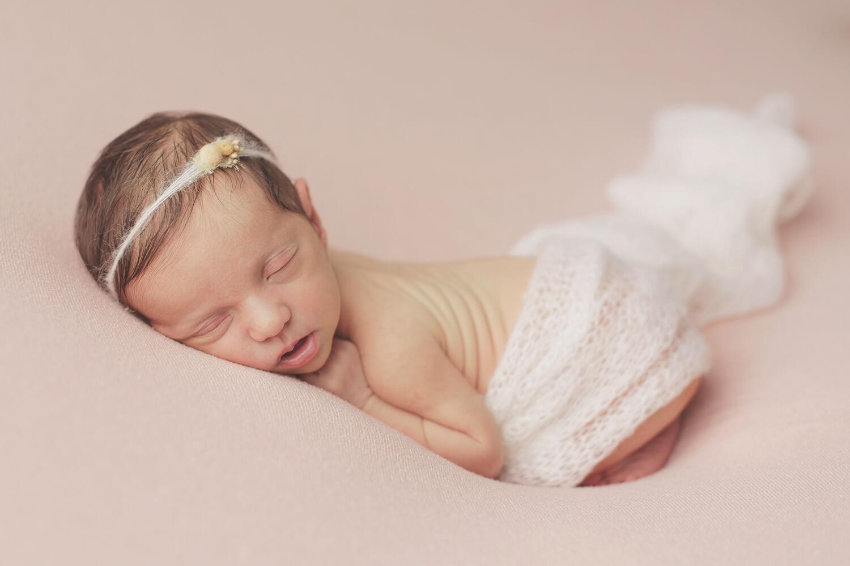 Photo d'un bébé fille qui dort sur un drap rose pendant séance