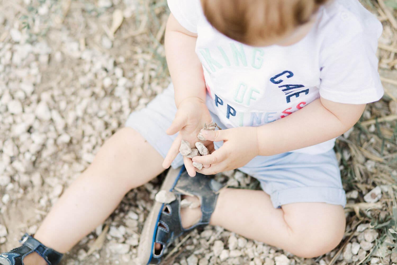 Photo-bebe-assise-joue-avec-cailloux