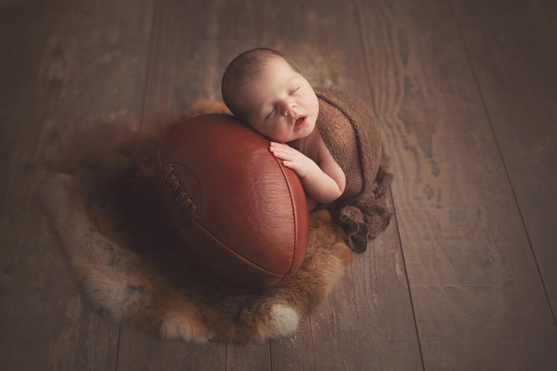 Photo d'un bébé qui pose sur un ballon de rugby pendant la séance nouveau-né