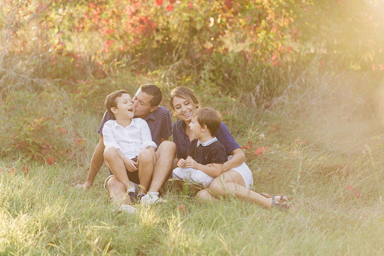 Photo-famille-assise-dans-herbe-rirent-ensemble