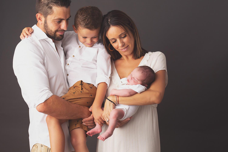 Photo d'une famille heureuse en regardant bebe pendant séance