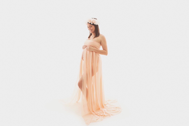 Photo d'une femme souriante en robe de grossesse pendant une séance studio