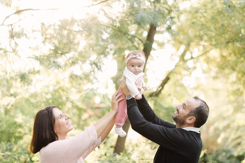 Photo-fille-sourit-soulevee-par-parents-seance-pleine-nature