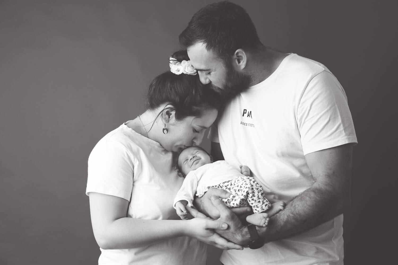 Photo-noir-blanc-bebe-sourit-dans-bras-parents