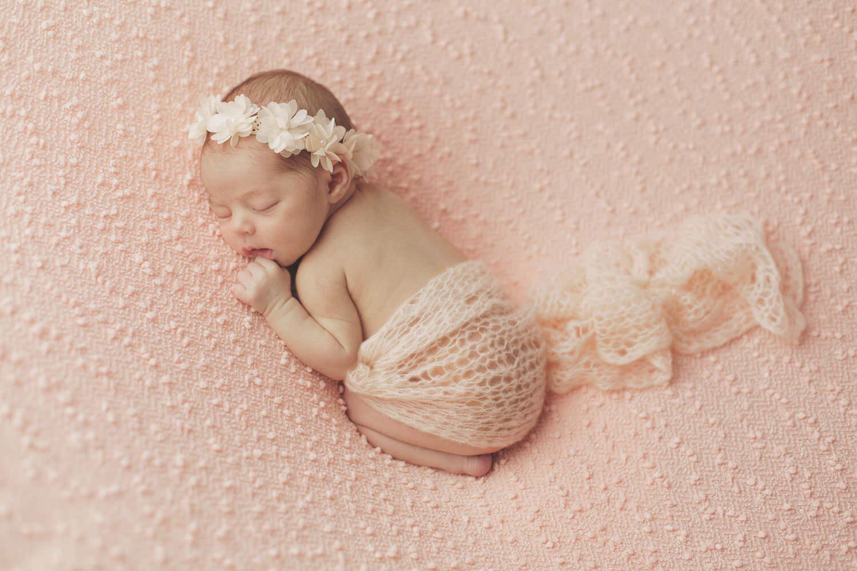Photo-nouveau-ne-dort-paisiblement-sur-drap-rose