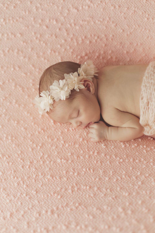 Photo-nouveau-ne-sur-drap-rose-bandeau-fleures