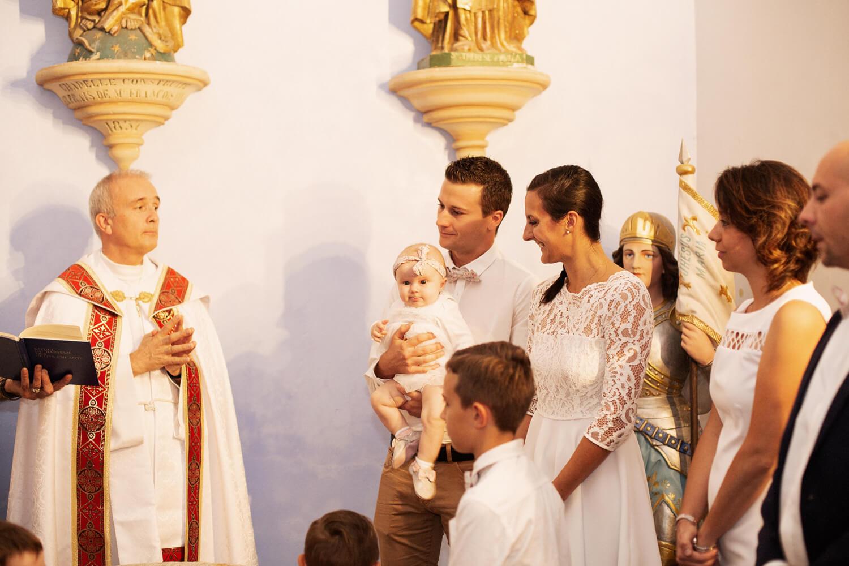 Photo-parents-fille-pretre-devant-fond-baptismal