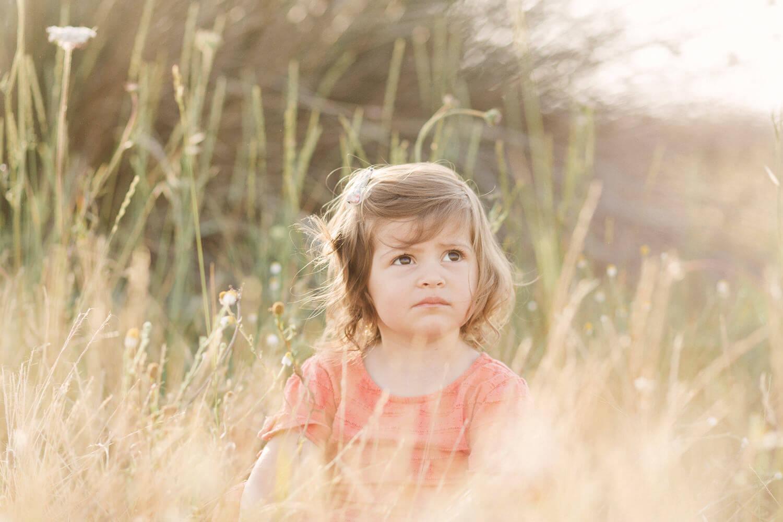 Photo-petite-fille-assisse-dans-hautes-herbes