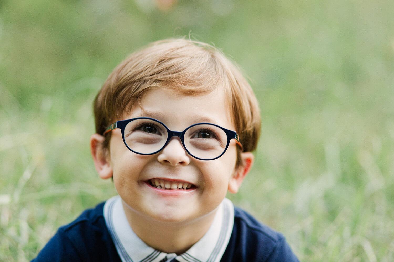 Portrait-petit-garcon-grand-sourire-assise-herbe